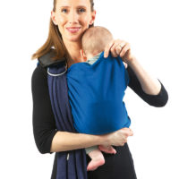 Keep holding baby up with your forearm. With the other hand, grab the upper hem and pull it up to the baby's neck. Check his position: Baby must be sitting with the material from the lower hem tucked behind his knees. His knees must bent and at hip-level.